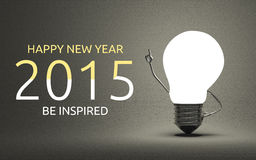 Happy New Year 2015, be inspired greeting card. Happy New Year 2015 and be inspired greeting card, light bulb character in moment of insight standing on gray Stock Photography