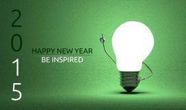 Happy New Year 2015, be inspired greeting card. Happy New Year 2015 and be inspired greeting card, light bulb character in moment of insight standing on green Stock Images