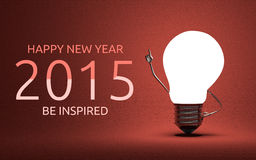 Happy New Year 2015, be inspired greeting card. Happy New Year 2015 and be inspired greeting card, light bulb character in moment of insight standing on red Royalty Free Stock Photos