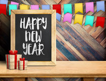 Happy new year on blackboard with gift and colorful flag banner Royalty Free Stock Photo