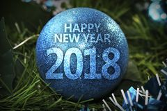 Happy new year 2018  blue christmas ball. New Year blue shiny Christmas tree ball with an text 2018 on the background of Christmas tree branches and tinsel Royalty Free Stock Images