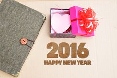 Happy New Year 2016 with book and gift on vintage brown background Royalty Free Stock Photos