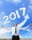 Happy new year 2017. Business man hug 2017 (white arrow cloud and blue sky on sunny day Royalty Free Stock Photo