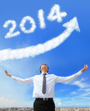 Happy new year 2014. Business man hug 2014 (white cloud and blue sky on sunny day Stock Image