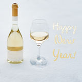 Happy New Year card. Bottle and glass of white wine chilled by snow. Stock Image