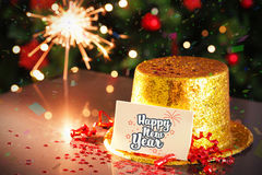 Happy new year card leaning on gold party hat Stock Photo
