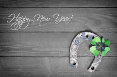 Happy New Year card with horseshoe and lucky clover. Happy New Year card with rusty horseshoe and lucky clover Stock Image