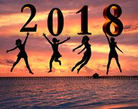 Happy new year card 2018. Silhouette young woman jumping on tropical beach over the sea and 2018 number with sunset background.  stock image