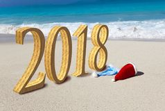 Happy new year card. Two New Year`s caps of Santa Claus on beach and inscription 2018 in the sand.  stock photos