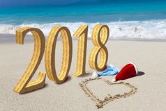 Happy new year card. Two New Year`s caps of Santa Claus on beach and on sand heart is drawn and inscription 2018.  stock photography