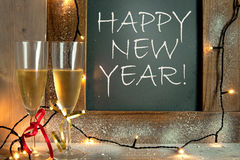Happy new year celebration. Champagne glasses next to chalkboard with happy new year greeting Stock Photos