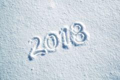 Happy new year greeting card on snow floor. Happy new year 2018 celebration message handwritten on the sunny fresh snow. Lovely Happy new Year Holiday greeting stock photo