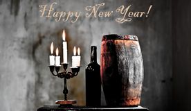 Happy new year from the cellar. The New Year`s Eve deserves a toast in the cellar between bottles and glasses Royalty Free Stock Images