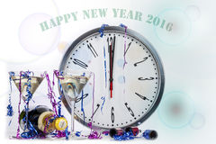 Happy new year champagne celebration showing a clock at midnight. With glasses and party poppers Royalty Free Stock Photos