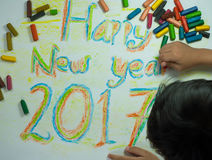 Happy new year 2017. A happy child with coloring pictures on the theme happy new year 2017 stock image