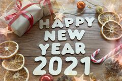Happy new year 2021. Christmas composition. New year`s layout on a dark wooden background. Cones, toys, gift, garland