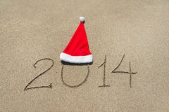 Happy new year 2014 with christmas hat on sandy beach - holiday Royalty Free Stock Photography
