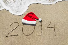 Happy new year 2014 with christmas hat on sandy beach Stock Images