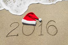 Happy new year 2016 with christmas hat on sandy beach stock photos