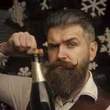 Happy New Year. Christmas man with beard on serious face open champagne. Santa claus man celebrating, alcohol. Party celebration and drink. Winter holiday and Stock Images