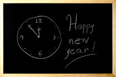 Happy new year clock on a blackboard Stock Photos