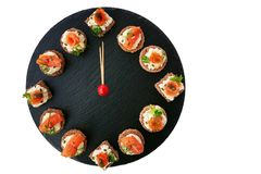 Happy New Year! Clock showing 12 o`clock, creative food idea with smoked salmon canapes. On black slate platter as clock face isolated on white background stock image