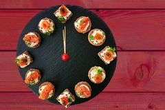 Happy New Year! Clock showing 12 o`clock, creative food idea with smoked salmon canapes. On black slate platter as clock face over dark red wooden background royalty free stock images