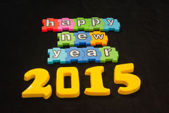 Happy New Year 2015. Colorful message in lower case white letters on colorful jigsaw style pieces saying   Happy New Year 2015   isolated on black background Royalty Free Stock Photo