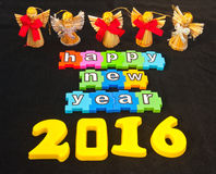 Happy New Year 2016. Colorful message in lower case white letters on colorful jigsaw style pieces saying   Happy New Year 2016  isolated on black background with Royalty Free Stock Images