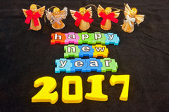 Happy New Year 2017. Colorful message in lower case white letters on jigsaw style colorful pieces saying   Happy New Year 2017   isolated on black background Royalty Free Stock Photos