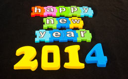 Happy New Year 2014. Colorful message in lower case white letters on jigsaw style pieces saying   Happy New Year 2014   isolated on black background Stock Images