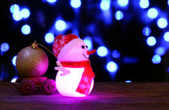 Happy New Year 2017 colors snowman on bokeh background. Dark evening colors Christmas and New Year`s card or poster with Snowman drags a truck ball on bokeh Stock Photography