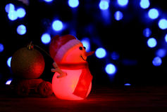 Happy New Year 2017 colors snowman on bokeh background. Dark evening red Christmas and New Year`s card or poster with Snowman drags a truck ball on bokeh Royalty Free Stock Image