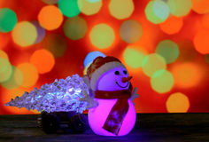 Happy New Year 2017 colors snowman and christmas tree on bokeh background. Dark evening Christmas and New Year`s card or poster with Snowman drags a truck Royalty Free Stock Image