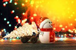 Happy New Year 2017 colors snowman and christmas tree on bokeh background. Dark evening Christmas and New Year`s card or poster with Snowman drags a truck glass Stock Photos