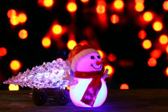 Happy New Year 2017 colors snowman and christmas tree on bokeh background. Dark evening Christmas and New Year`s card or poster with Snowman drags a truck Royalty Free Stock Photos