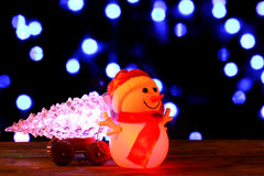 Happy New Year 2017 colors snowman and christmas tree on bokeh background. Dark evening Christmas and New Year`s card or poster with Snowman drags a truck Stock Photo
