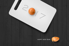 2017 Happy New Year Concept  background 05. 2017 Happy New Year Concept, 2017 Text on Plastic Antiseptic Cutting Board With Onion on Grey Wall Texture. Selection Royalty Free Stock Images