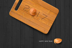 2017 Happy New Year Concept background 04. 2017 Happy New Year Concept, 2017 Text on Wooden Antiseptic Cutting Board With Onion on Grey Wall Texture. Selection Stock Illustration