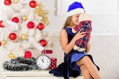 Happy new year concept. Kid sit near christmas tree hold teddy bear gift. Best gift ever. Excitement replaced with. Strong feeling satisfaction. Little girl royalty free stock photo