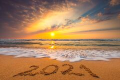 Happy New Year 2021, lettering on the beach. Written text on the sea beach at sunrise