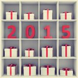 Happy New Year concept. 2015 new year concept. Red number characters and gift boxes placed on white square book shelf Royalty Free Stock Image
