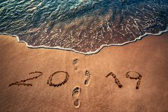 Happy New Year 2019, footprints, sand and wave royalty free stock photography