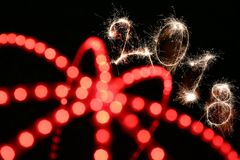 Happy new year 2018 concept. 2018 sign written with sparkle firework on black background with blurred red lines, happy new year 2018 concept Stock Photo