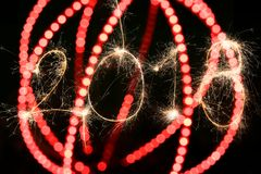 Happy new year 2018 concept. 2018 sign written with sparkle firework on black background with blurred red lines, happy new year 2018 concept Royalty Free Stock Image