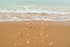 Happy New Year 2018. Concept: The waves are about to cover 2017, both years placed with seashells on the beach Royalty Free Stock Photo