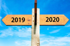 Happy New Year 2020 conceptual image. Wooden signpost with two opposite arrows over clear blue sky, year 2019 and 2020 signs, Happy New Year conceptual image Stock Images