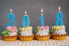 Happy new 2018 year, cupcakes with blue number candles. On gray background Stock Photography