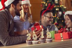 Happy New 2019 Year. Cupcakes with lit candles shaped as numbers 2019 placed on a coffee table with group of friends celebrating and exchanging gifts in the stock image