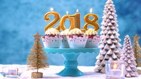 Happy New Year 2018 cupcakes. On a modern stylish, festive, blue gold and white Winter theme table setting, close up with copy space Royalty Free Stock Photos